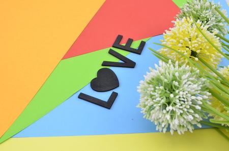 position d amour: mot amour avec le symbole de l'amour en position color.vertical noir avec vert, blanc et jaune fleur artificielle sur fond orange, rouge, bleu et vert