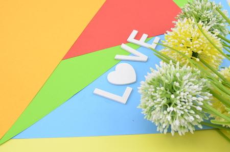position d amour: mot amour avec le symbole de l'amour en blanc la position color.vertical de vert, blanc et jaune fleur artificielle sur fond orange, rouge, bleu et vert Banque d'images