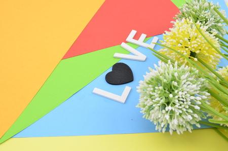 position d amour: mot amour avec le symbole de l'amour noir blanc police position de color.vertical de vert, blanc et jaune fleur artificielle sur l'orange, rouge, bleu et fond vert