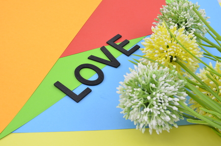 position d amour: word love black color in vertical position  with green, white and yellow artificial flower on orange, red, blue and green background
