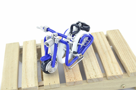 image concept wired handcraft mini scooter on wooden pallet isolated white background