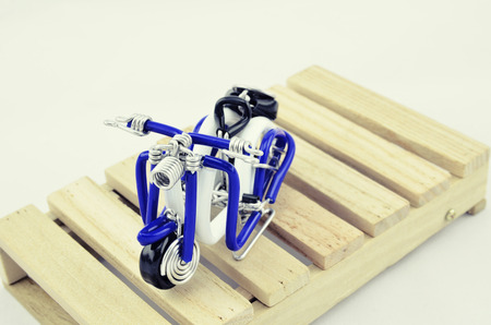 wired: vantage look mini scooter made from white, blue and black wired placed on wooden pallet Stock Photo