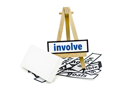 involve: concept involve word on wooden stand.random cutted print paper and empty canvas frame isolated white background