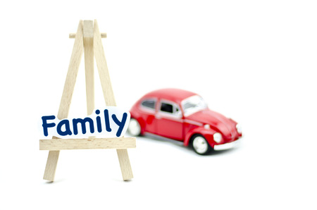 collectible: KUALA LUMPUR, MALAYSIA 17 AUGUST 2015 : image with word family on tripod stand made from wood and Volkswagon Beetle collectible model car