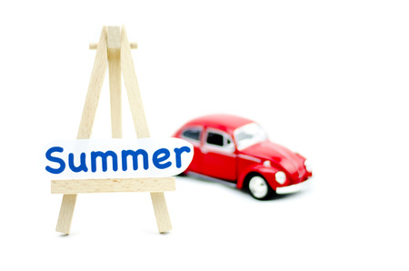 collectible: KUALA LUMPUR, MALAYSIA 17 AUGUST 2015 : image with word summer on tripod stand made from wood and Volkswagon Beetle collectible model car