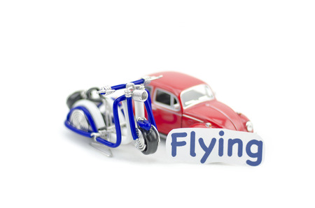 collectible: KUALA LUMPUR, MALAYSIA 17 AUGUST 2015 : image with word flying printed on paper. Volkswagon Beetle collectible model car and wired handcraft scooter.