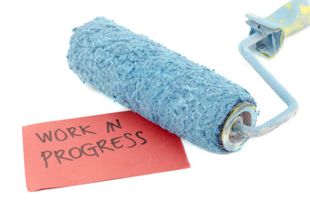 printed work: cropped image roller paint brush in blue color. word work in progress printed on red paper isolated white background Stock Photo