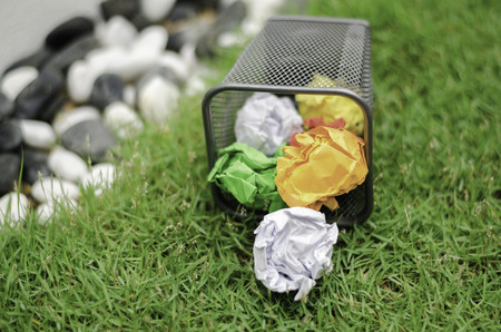 wastebasket: Crumpled colored paper on metal bin.green grass and blurred image