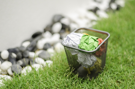 wastebasket: colourful waste paper on garbage can. surrounding by green grass, black and white decoration rock