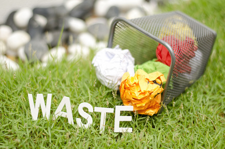 discard: blurred image concept, crumple color paper on metal bin, green grass and blur background Stock Photo