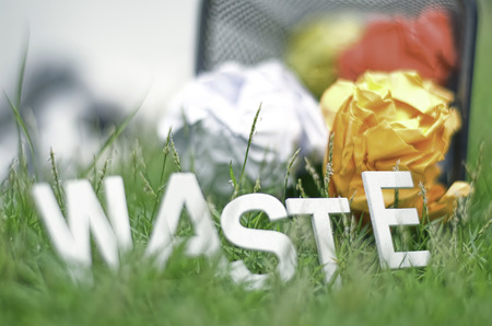 waste basket: blurred and cropped closeup image crumpled coloured paper with word WASTE made from wood on green grass