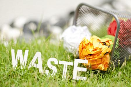 discard: blurred image concept orange colour paper. crumple on green grass