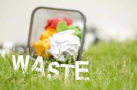 thrash: blurred image of word waste made from wood placed on green grass. ball used colour paper in thrash can and blur background