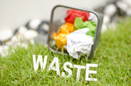 thrash: blurred image of word waste made from wood in arc position placed on green grass and centered. used colour paper in thrash can and blur background; Stock Photo