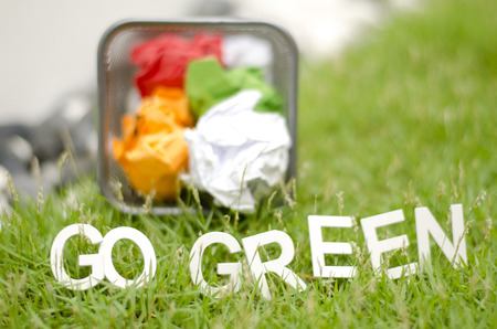 crumple: blurred image of crumple paper in thrash can with alphabet GO GREEN on green grass