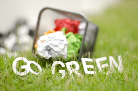 thrash: closeup blurred image concept. used color paper in thrash can with alphabet GO GREEN on green grass