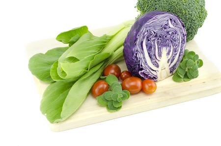 leaf vegetable: cropped image of green leafy raw Bak Choi  Chinese Cabbage, purple cabbage, cherry tomatoes and mint on wooden cutting board, isolated on white background