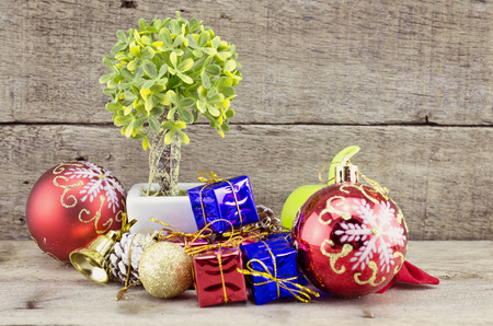 retro look Christmas decorations with red ball,green ball,red ribbon,bell,samll tree on white pot, and artificial flower. aged and dirty wood plank with texture Stock Photo