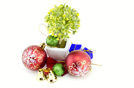 samll: group image of Christmas decorations with red ball,green ball,red ribbon,bell,samll tree on white pot, and artificial flower isolated on white background