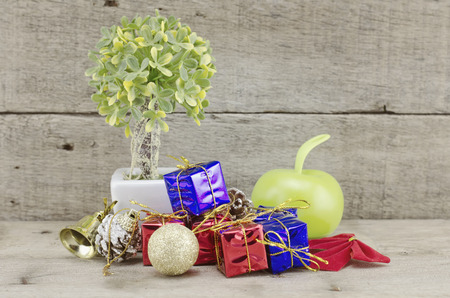 samll: retro look Christmas decorations with red ball,green ball,red ribbon,bell,samll tree on white pot, and artificial flower. aged and dirty wood background with texture Stock Photo