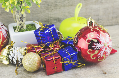 festive pine cones: cropped image of big red ball, artificial tree, pine cone, golden bell and gift box on wooden floor Stock Photo