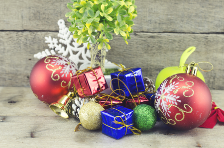 blue gift box: cropped image of red ball, artificial tree on pot, pine cone, white snowflakes, golden bell, red and blue gift box on wooden floor Stock Photo