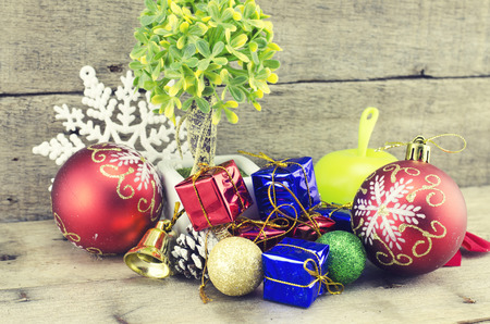 blue gift box: cropped image of big red ball, artificial tree, pine cone, white snowflakes, golden bell, red and blue gift box on wooden floor