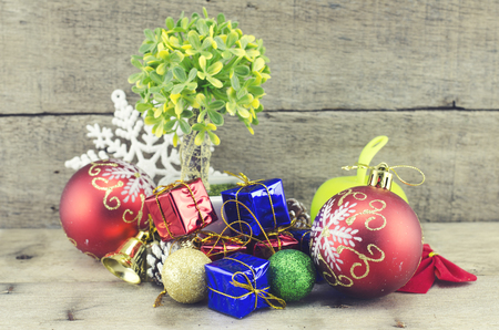 blue gift box: retro look and cropped image of red ball, artificial tree on pot, pine cone, white snowflakes, golden bell, red and blue gift box on wooden floor