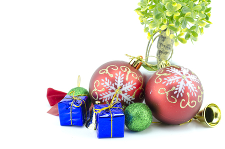 blue gift box: two red ball christmas ornamen with blue gift box, green ball, golden bell, ribbon and artificial green tree. isolated on white background