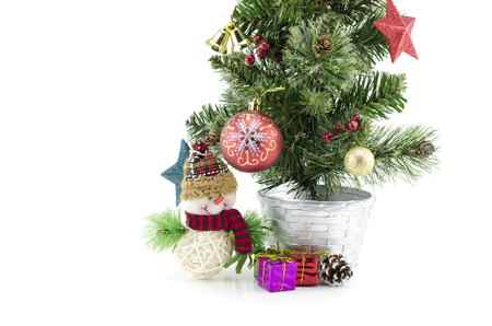 fabrick: closeup and cropped  image of christmas tree  with santa claus , gift box, red ball,pinecone and golden ball isolated on white background.copyspace on the left Stock Photo