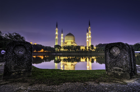 islamic wonderful: one of the beautiful iconic mosque at Malaysia during sunset with reflection on the lake Stock Photo