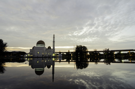 islamic wonderful: beautiful mosque at sunset sunrise with reflection on the lake and cloudy sky