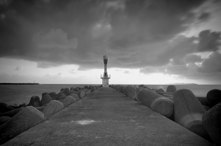 monsoon clouds: black and white image of lighthouse with dark and dramatic clouds during monsoon season.concrete breakwater and wall. Stock Photo