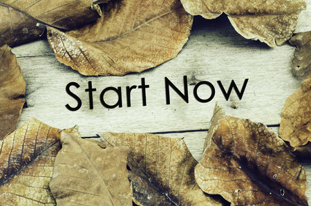 job deadline: word START NOW surrounded by dry leaves .old wooden background and retro look theme