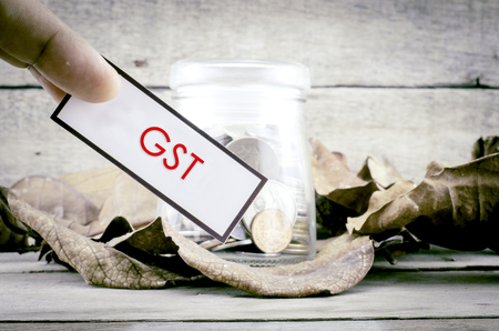 image concept cropped finger holding white label with black frame with word GST. background with coin in glass jar surrounded by dry leaves and wood Stock Photo