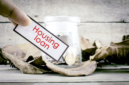 housing loan: image concept cropped finger holding white card with black frame with word HOUSING LOAN. background with coin in glass jar surrounded by dry leaves and wood.