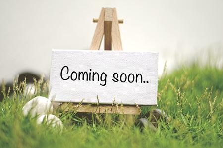 image concept canvas op houten statief met woord BINNENKORT BINNENKORT. Wazig en zachte focus achtergrond met groen gras en witte steen Stockfoto