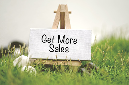 prospecting: image concept white frame canvas on wooden tripod with word GET MORE SALES. Blurred and soft focus background with green grass and white stone