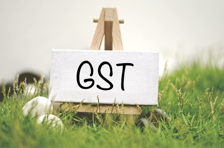 image concept white frame canvas on wooden tripod with word GST. Blurred and soft focus background with green grass and white stone
