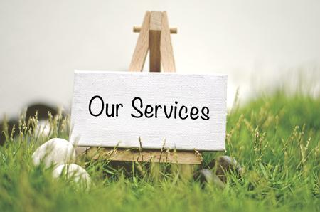 イメージ コンセプト ホワイト フレーム キャンバス単語当社サービスと木製の三脚。緑の芝生と白い石でぼやけとソフト フォーカスの背景