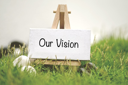 our vision: image concept white frame canvas on wooden tripod with word OUR VISION. Blurred and soft focus background with green grass and white stone