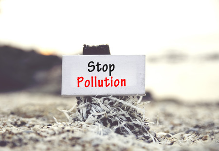 stop pollution: concept image, word STOP POLLUTION on white canvas frame with blurred beach and clam shell background.