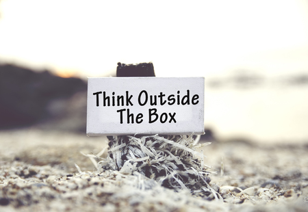think out: concept image, word THINK OUT SIDE THE BOX on white canvas frame with blurred beach and clam shell background.