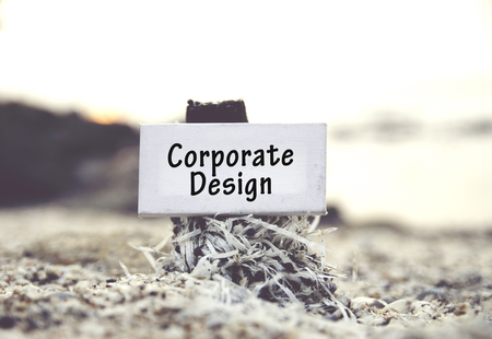 gobierno corporativo: concept image, word CORPORATE DESIGN on white canvas frame with blurred beach and clam shell background.