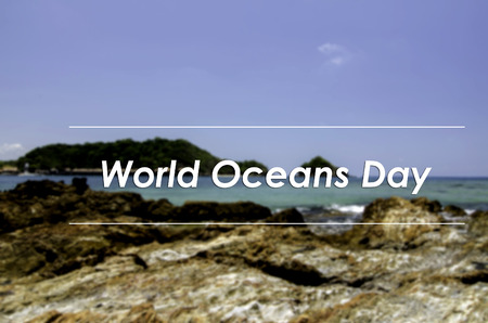 the oceans: image concept with word WORLD OCEANS DAY.blurred background Rocky shore with blue sky background and clear water at sunny day. Stock Photo
