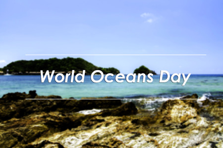 the oceans: image concept with word WORLD OCEANS DAY.blurred background rocky sea view at the beach with island surrounded by clear water and blue sky background.