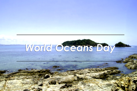 the oceans: image concept with word WORLD OCEANS DAY.blurred background rocks and turquoise water at tropical seashore surrounded by clear water and blue sky Stock Photo