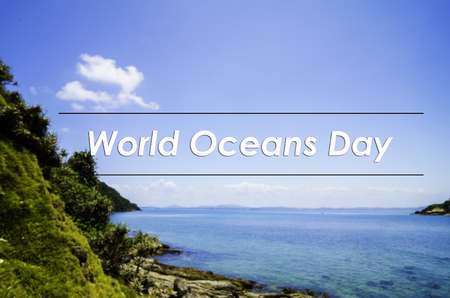 the oceans: image concept with word WORLD OCEANS DAY.blurred background the cliff covered with thick foliage and turquoise color sea water surrounding the  Island.