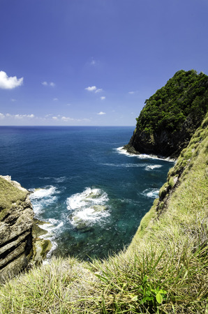 cliff top: tropical ocean view from the cliff top .small wave hitting the rock with blue sky background at sunny day.