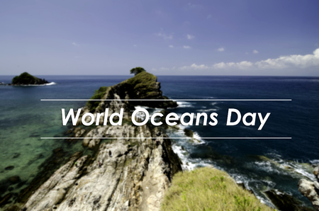 the oceans: image concept with word WORLD OCEANS DAY.blurred background view from the top hill view,tropical island surrounded by clear water and blue sky at sunny day